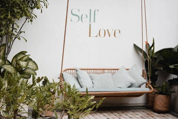 "Hanging sofa with the words ""self-love"" in the background"